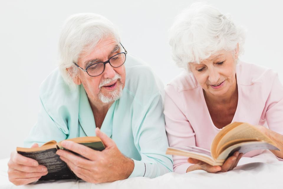 """Husband and wife reading and chatting"" stock image"
