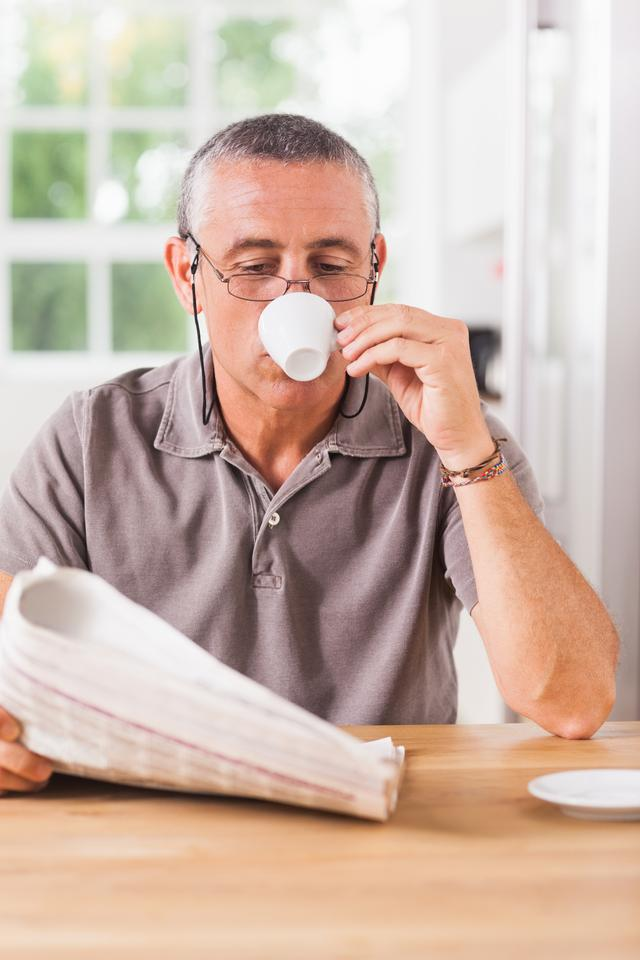 """Man reading newspaper and drinking espresso"" stock image"