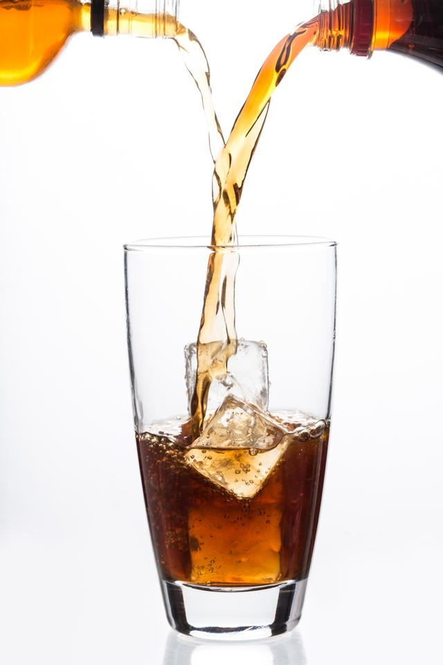 """""""Two bottles pouring into a glass with ice cube"""" stock image"""