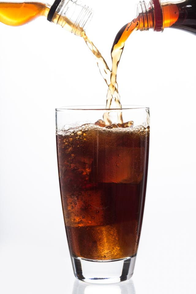 """""""Soda and alcohol filling a glass with ice cube"""" stock image"""