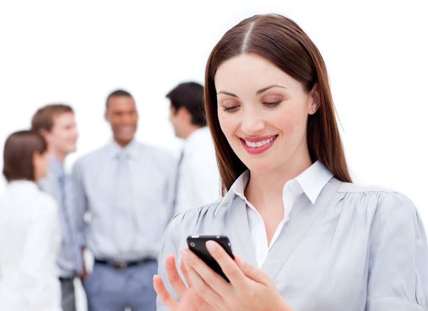 """Smiling businesswoman sending a text"" stock image"