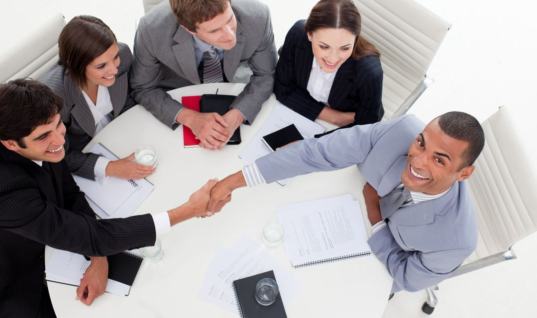 """""""Business people smiling at the camera while closing a deal"""" stock image"""