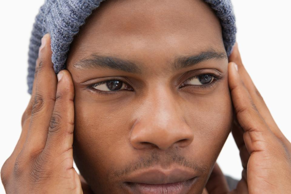 """Man in beanie hat looking unhappy"" stock image"