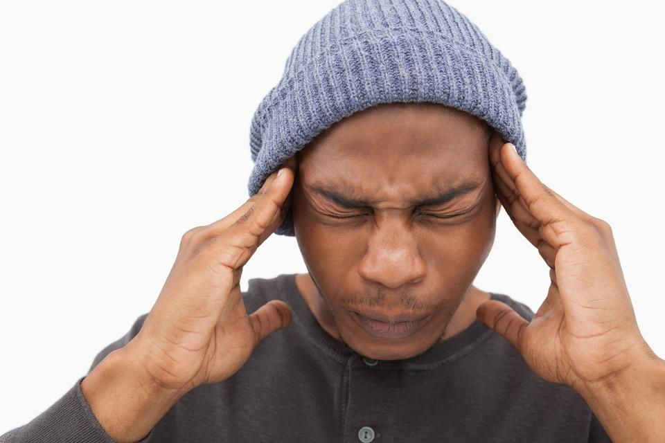 """Man in beanie hat wincing with pain of headache"" stock image"