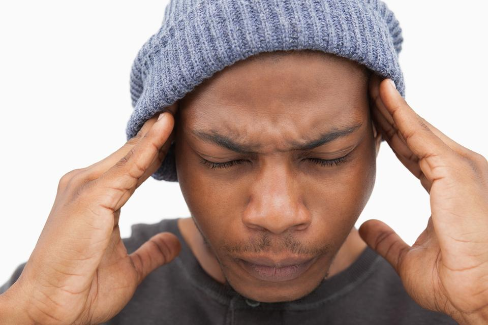 """Man in beanie hat grimacing with pain of headache"" stock image"