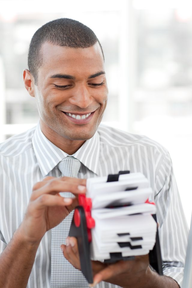 """""""Attractive businessman consulting a business card holder"""" stock image"""