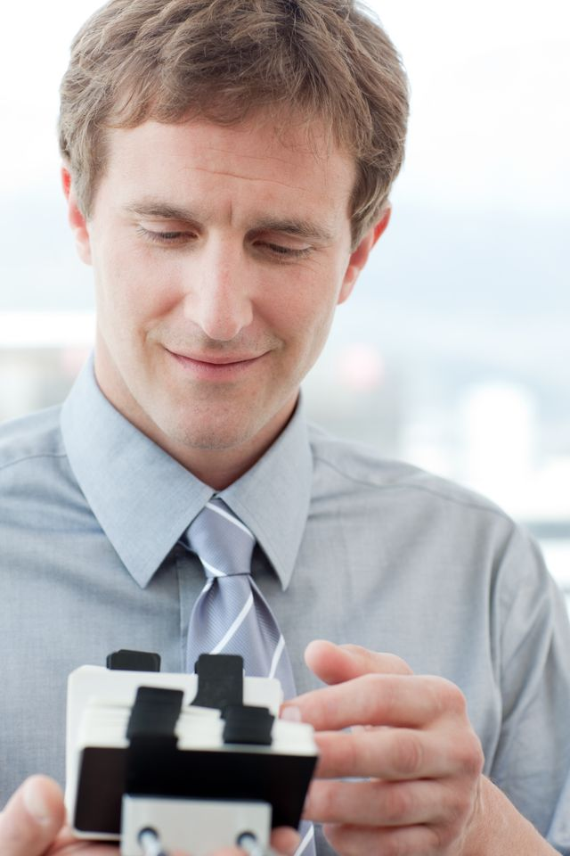 """""""Businessman consulting a business card holder"""" stock image"""