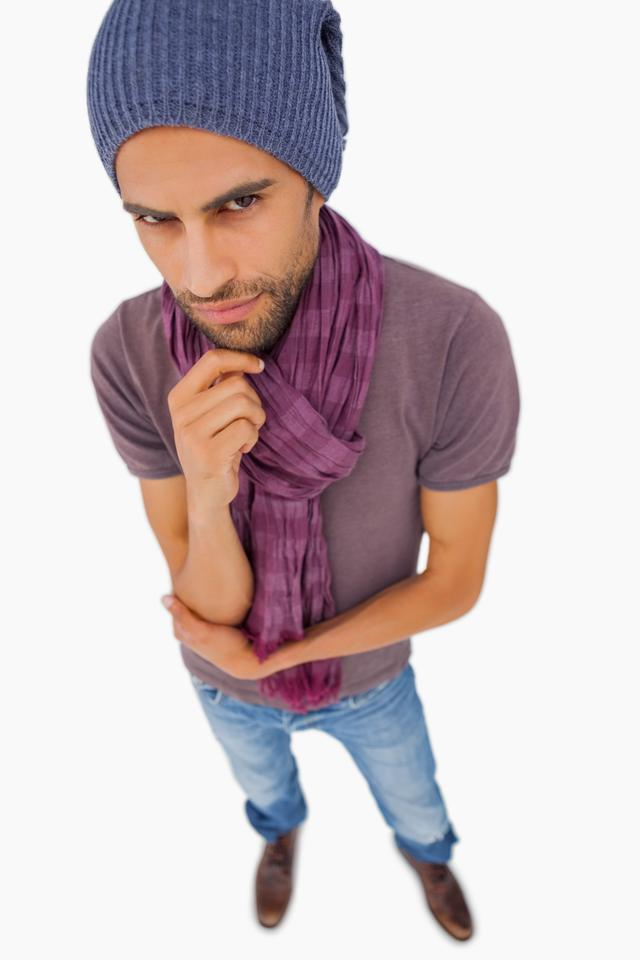 """Thinking man wearing beanie hat and scarf"" stock image"