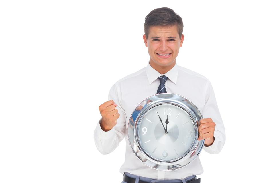 """Fearful businessman holding and looking at clock"" stock image"