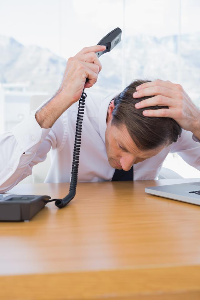 """Irritated businessman holding the telephone"" stock image"