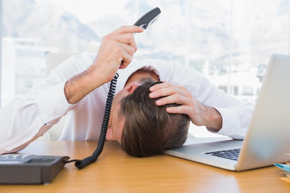 """Irritated businessman holding the phone"" stock image"