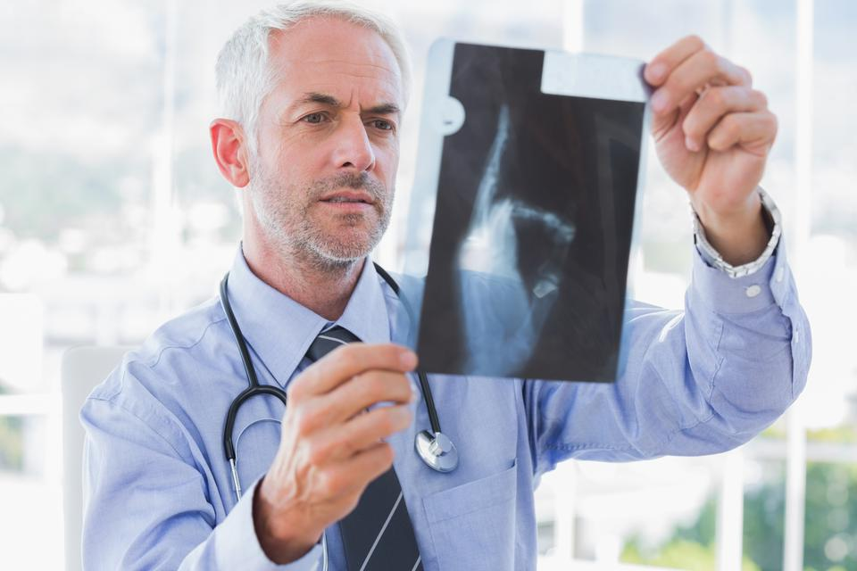 """Handsome doctor examining an xray"" stock image"