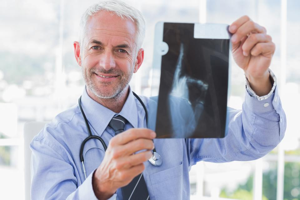"""Smiling doctor holding a radiography"" stock image"
