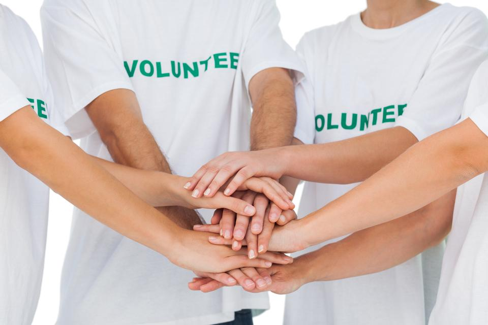"""Group of volunteers putting hands together"" stock image"