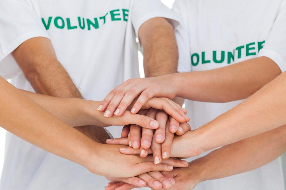 """Volunteers piling up their hands together"" stock image"