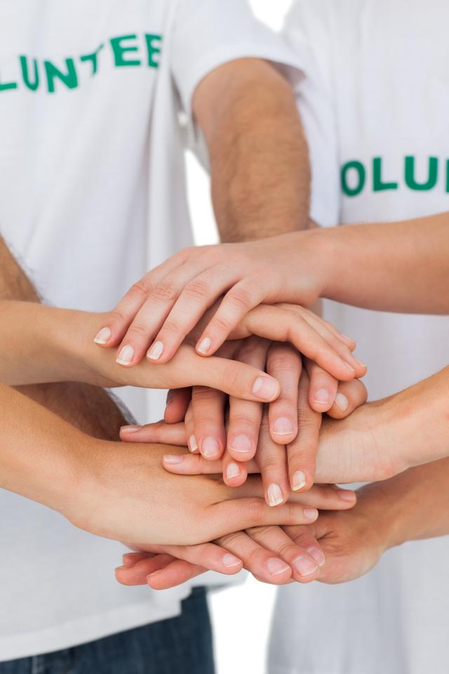 """Volunteers putting hands together"" stock image"