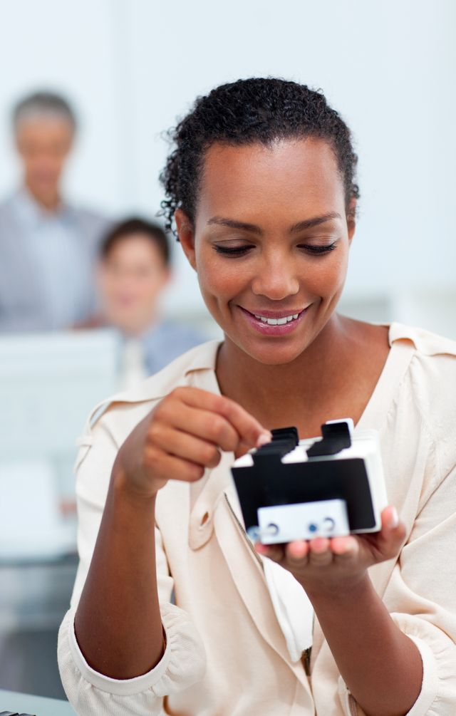 """""""Smiling businesswoman consulting a business card holder"""" stock image"""