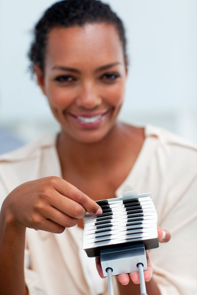 """""""Confident businesswoman consulting a business card holder"""" stock image"""
