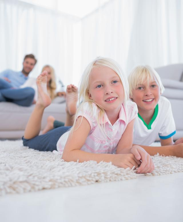 """""""Cute children lying on the carpet smiling at camera"""" stock image"""