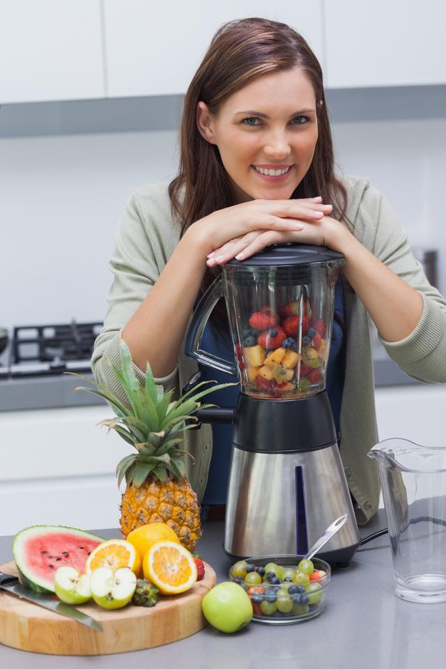 """Woman leaning on her blender"" stock image"