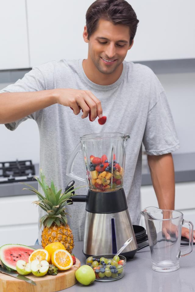 """Man putting a strawberry in the blender"" stock image"