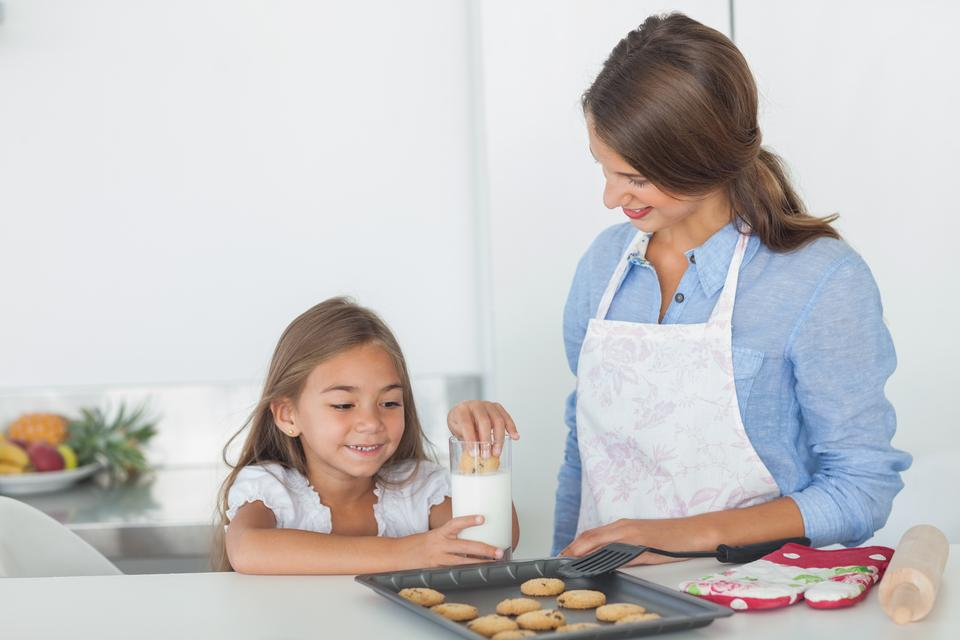 """Little girl dunking a cookie into a glass of milk"" stock image"