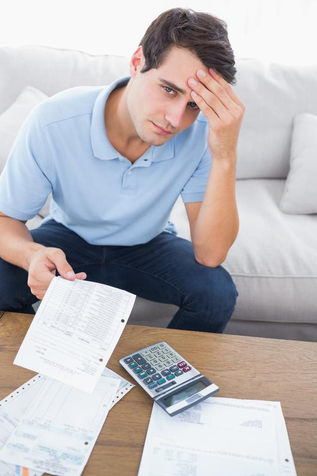 """Fearful man doing his accounts with a calculator"" stock image"