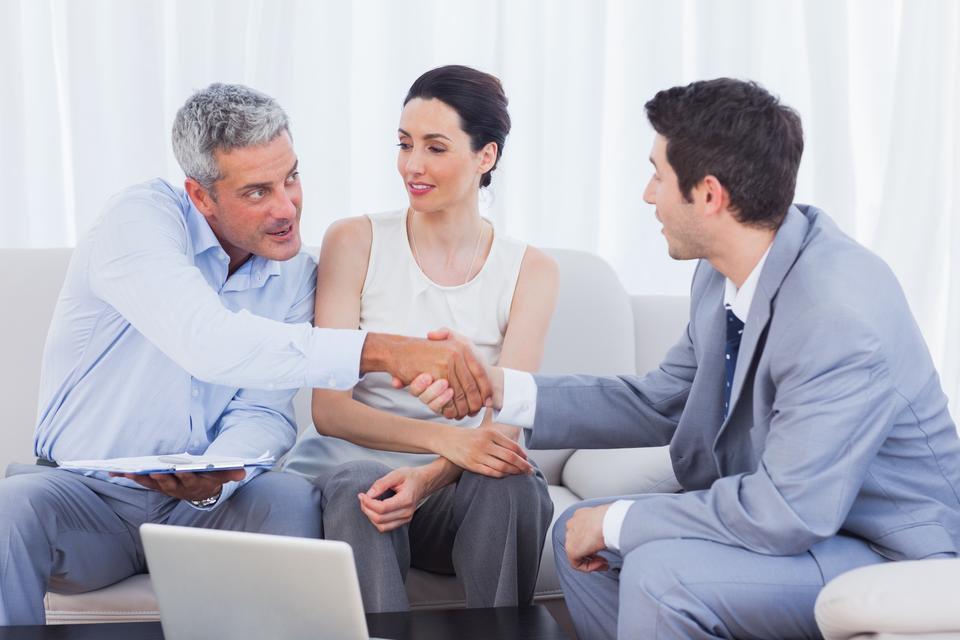 """""""Salesman closing a deal with a smiling couple"""" stock image"""