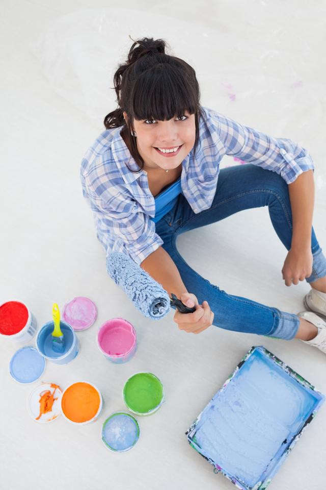 """""""Happy woman sitting on floor with paint"""" stock image"""