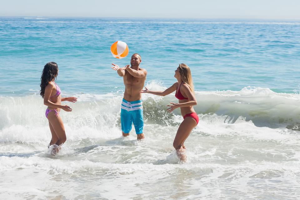 """Cheerful friends playing with a beachball in the sea"" stock image"