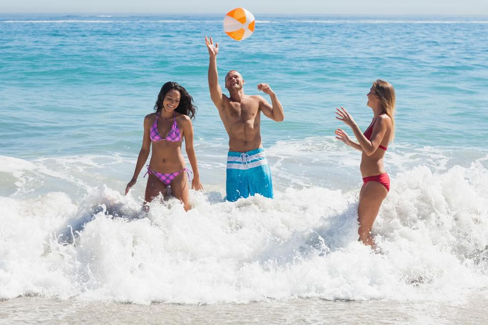 """Happy friends playing with a beachball in the sea"" stock image"