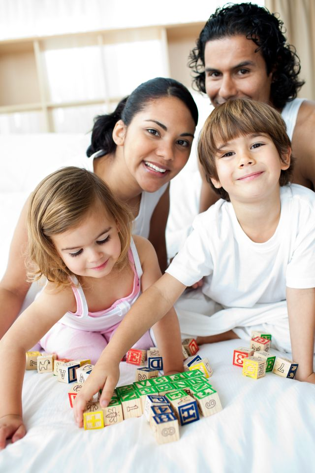 """Young family having fun with alphabetics blocks"" stock image"