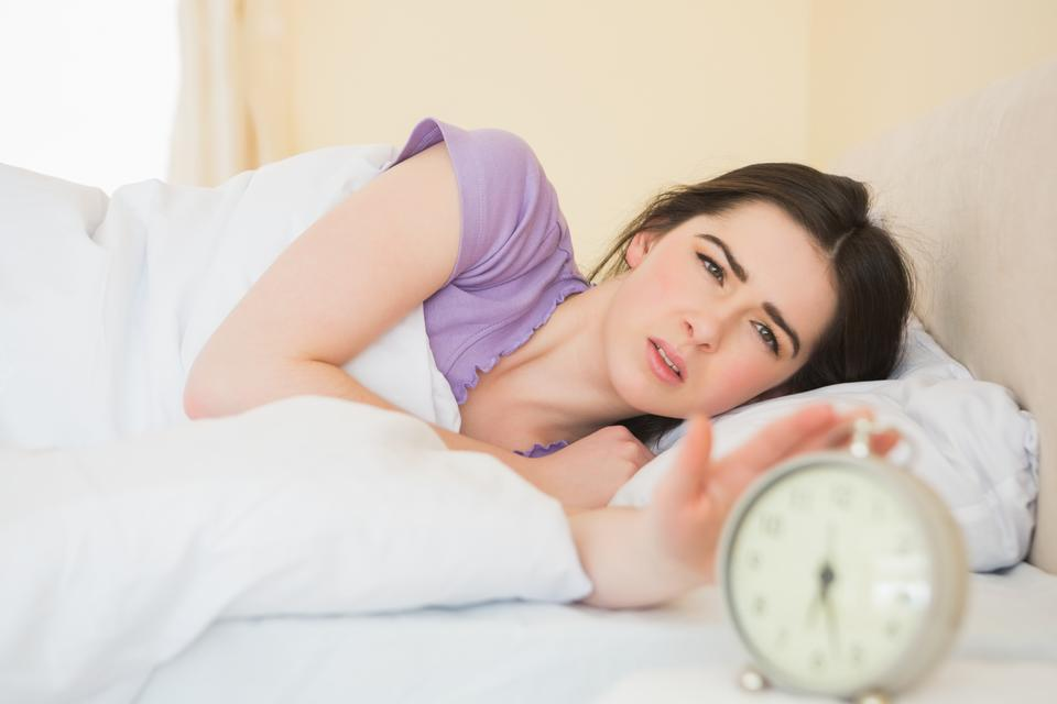 """Irritated girl waking up in her bed"" stock image"
