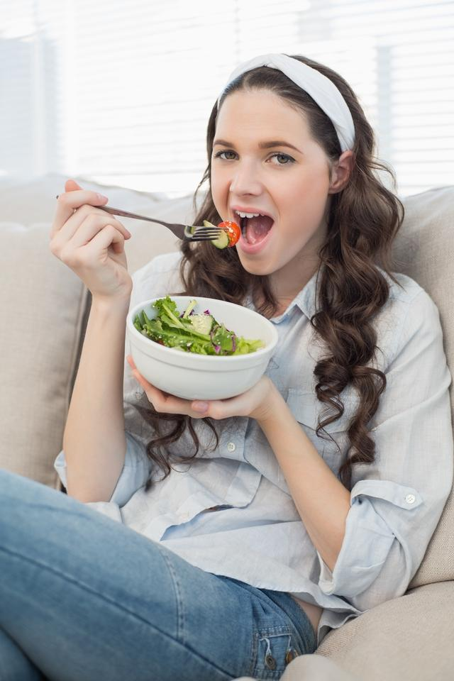 """""""Cute casual woman on cosy couch eating salad"""" stock image"""