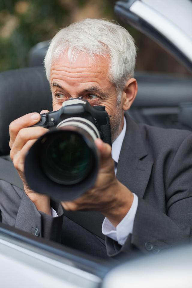 """""""Mature paparazzi taking picture with his professional camera"""" stock image"""