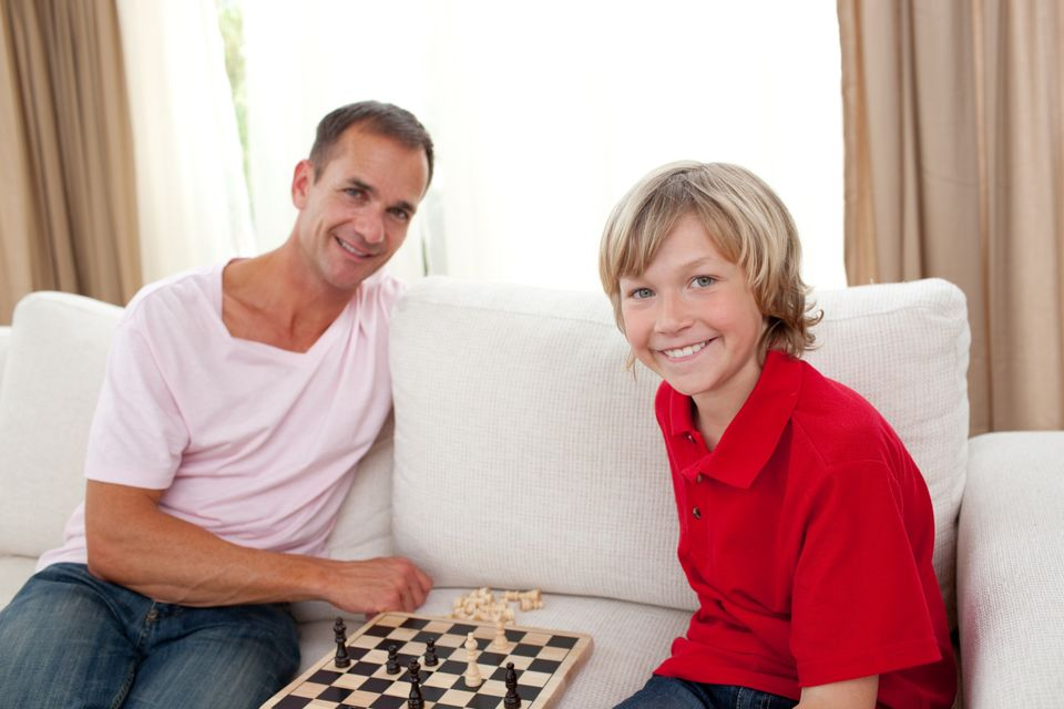 """""""Caring father playing chess with his son"""" stock image"""