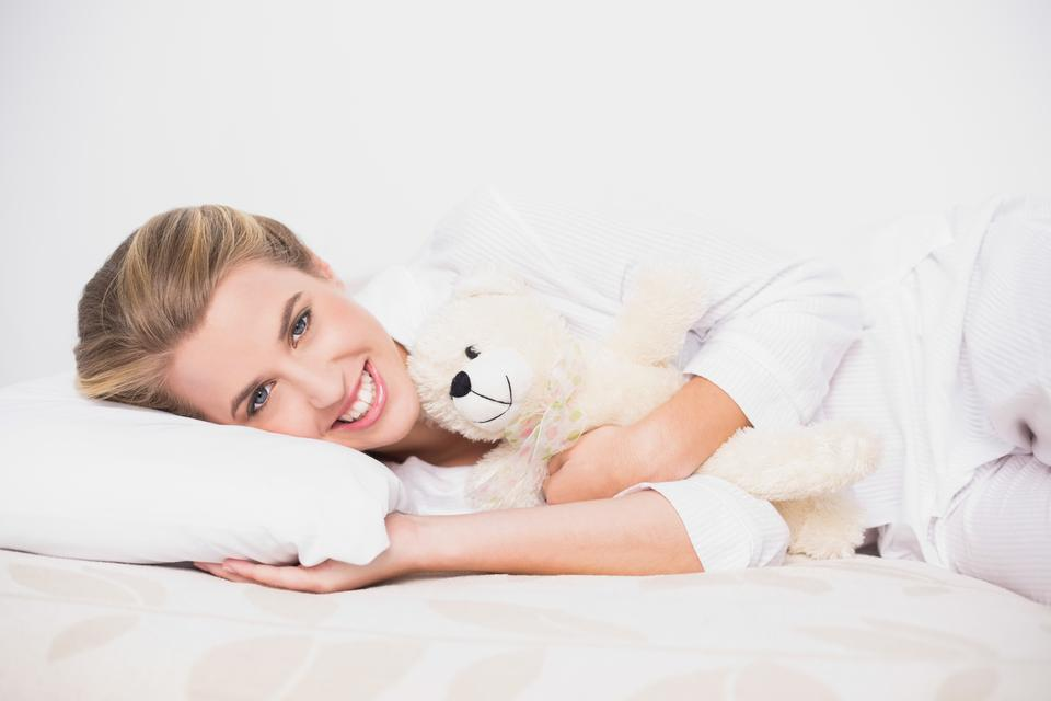 """""""Cheerful cute model lying on cosy bed with teddy bear"""" stock image"""