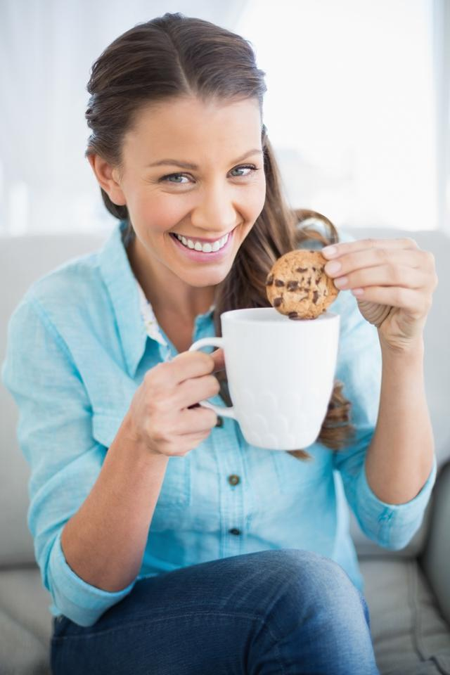 """Smiling woman dunking cookie in coffee"" stock image"