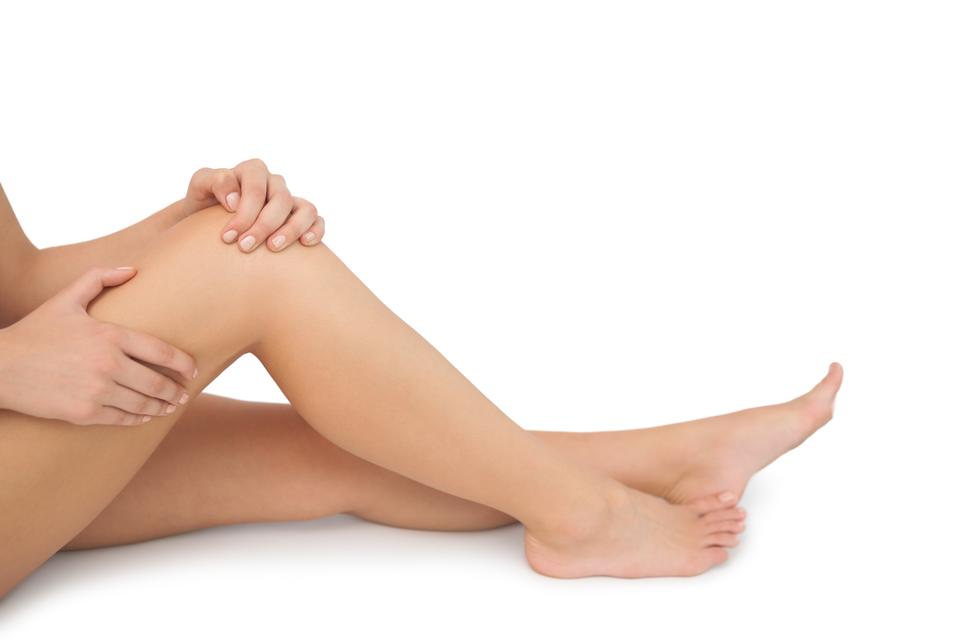 """""""Mid section of young woman sitting on floor touching her injured knee"""" stock image"""