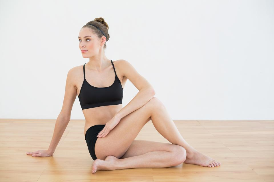 """Cute toned woman stretching her body sitting on floor"" stock image"