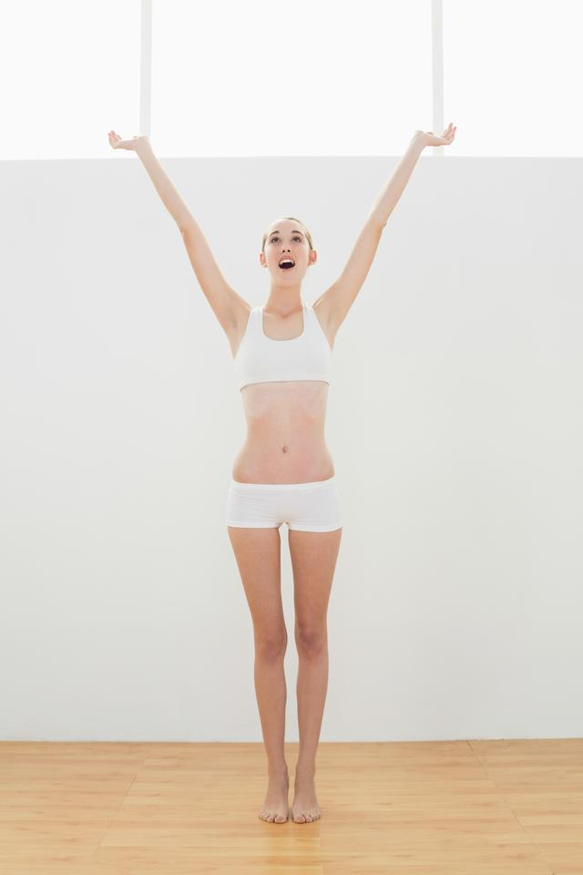 """Cute toned woman raising her arms for stretching her body"" stock image"