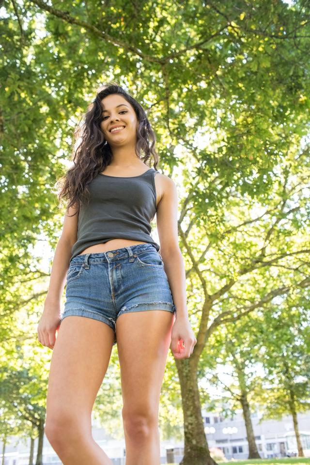 """Casual gorgeous brunette standing on grass"" stock image"