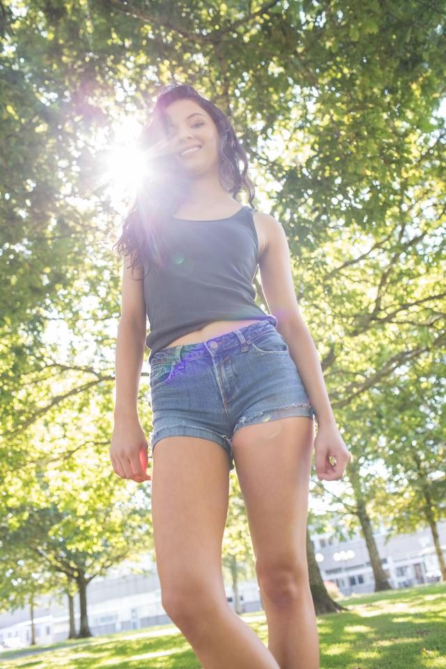 """Casual gorgeous brunette standing on grass in sunlight"" stock image"