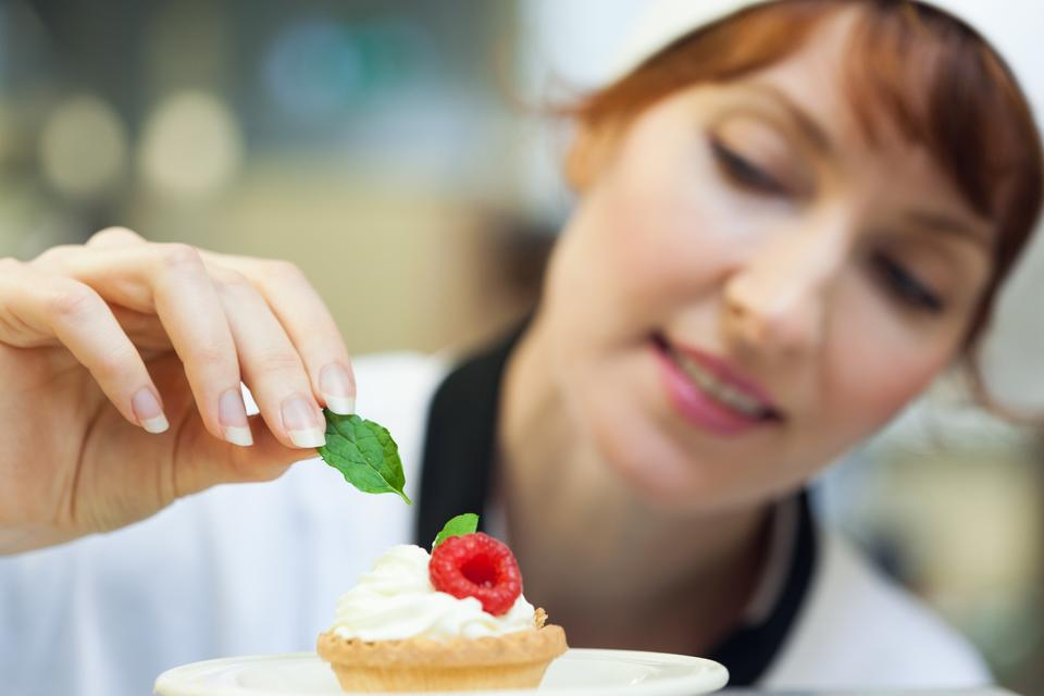 """""""Happy head chef putting mint leaf on little cake"""" stock image"""