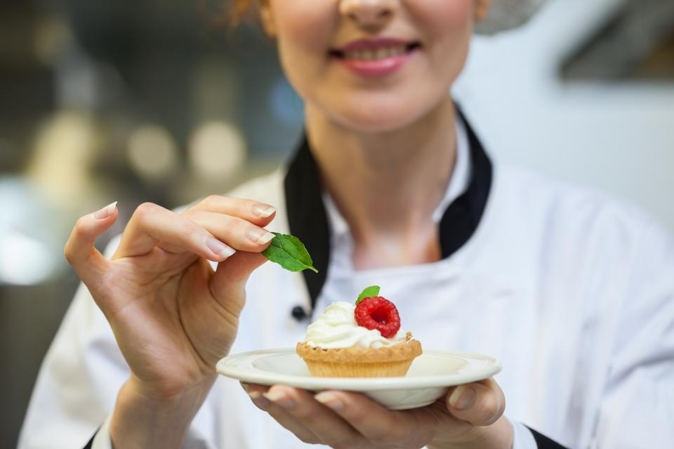 """""""Happy head chef putting mint leaf on little cake on plate"""" stock image"""
