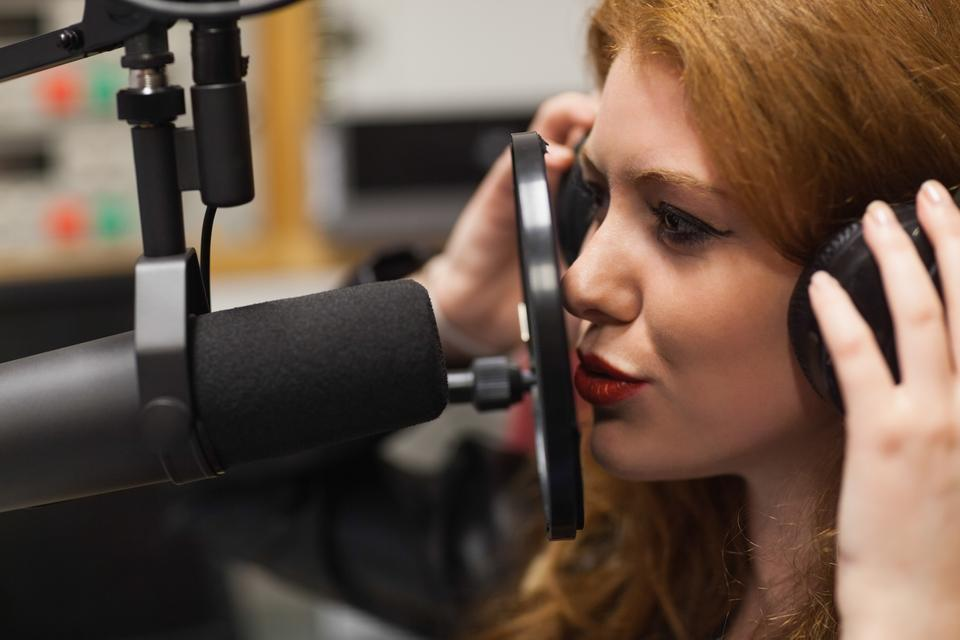 """Focused beautiful singer recording a song"" stock image"