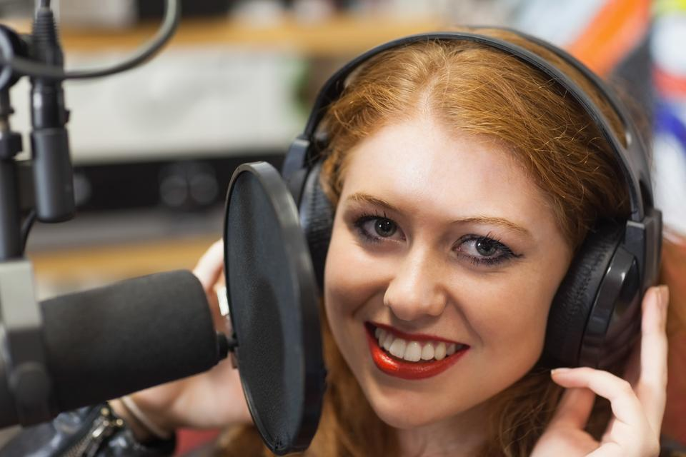 """Smiling beautiful singer recording a song"" stock image"