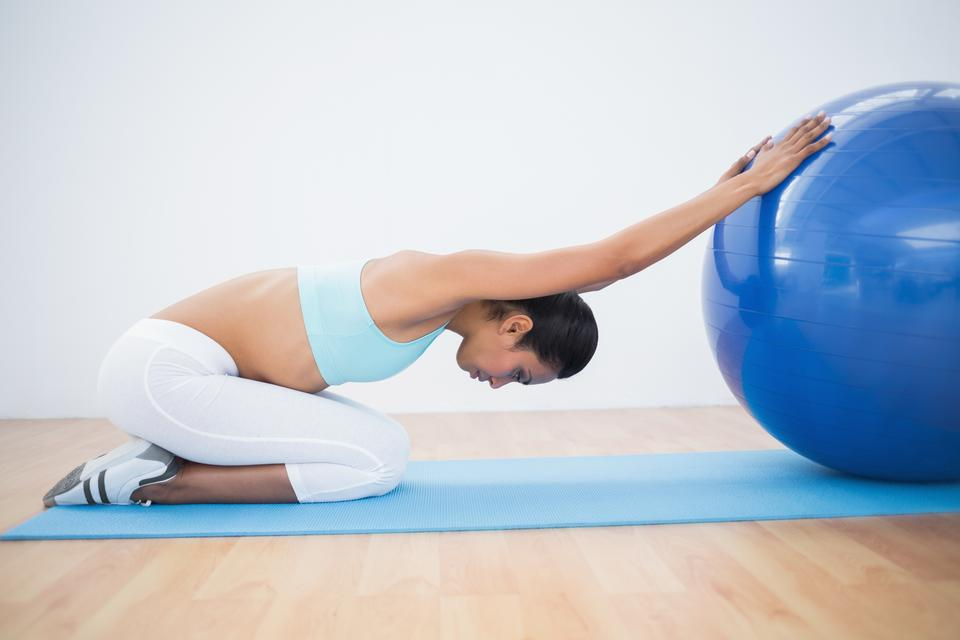 """Lovely toned woman stretching her body with exercise ball"" stock image"