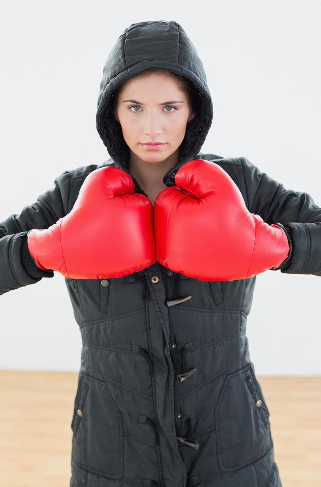 """""""Serious woman in red boxing gloves and black hood at fitness studio"""" stock image"""