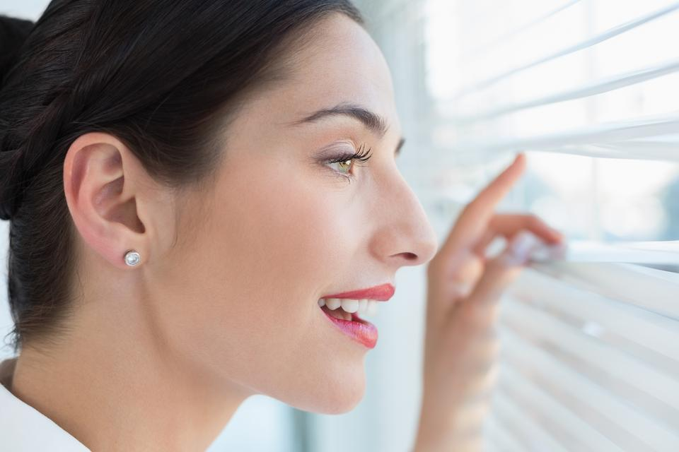 """""""Smiling business woman peeking through blinds at office"""" stock image"""